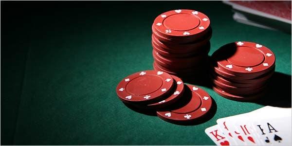 Foto van pokertafel met daarop speelkaarten en rode pokerchips